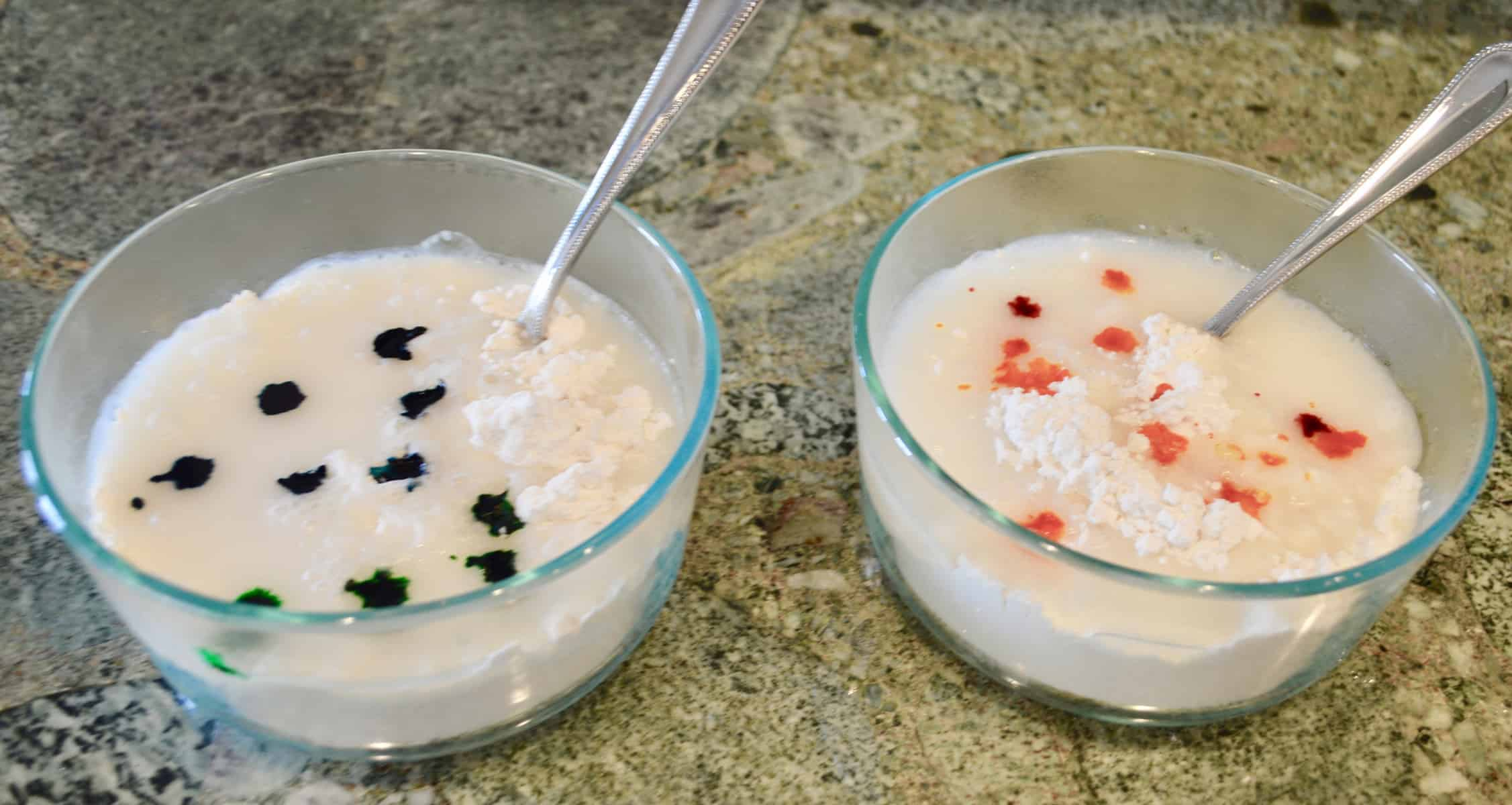 Two bowls of water and flour with food coloring drops on a countertop