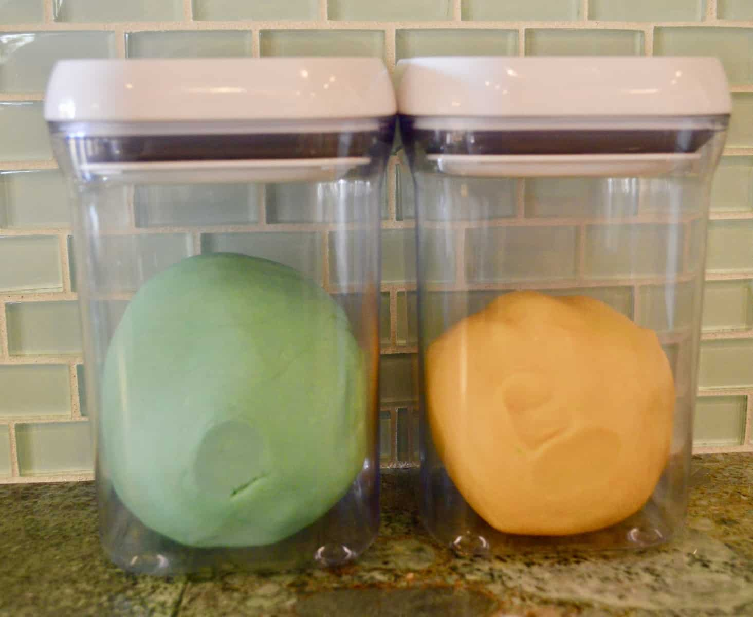 teal and orange play doh in a two airtight containers
