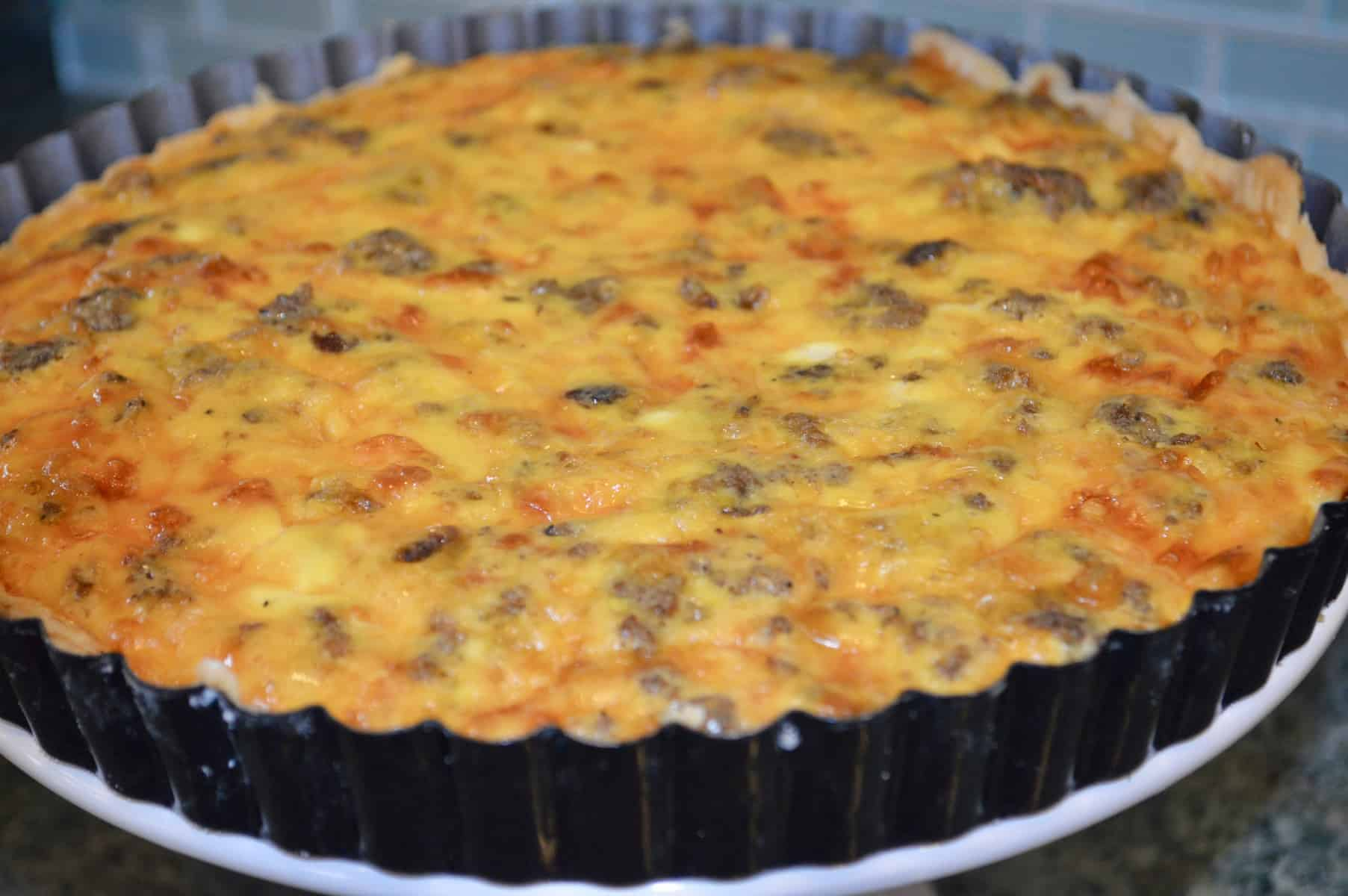Egg and Sausage tart in a pan on a white pedestal