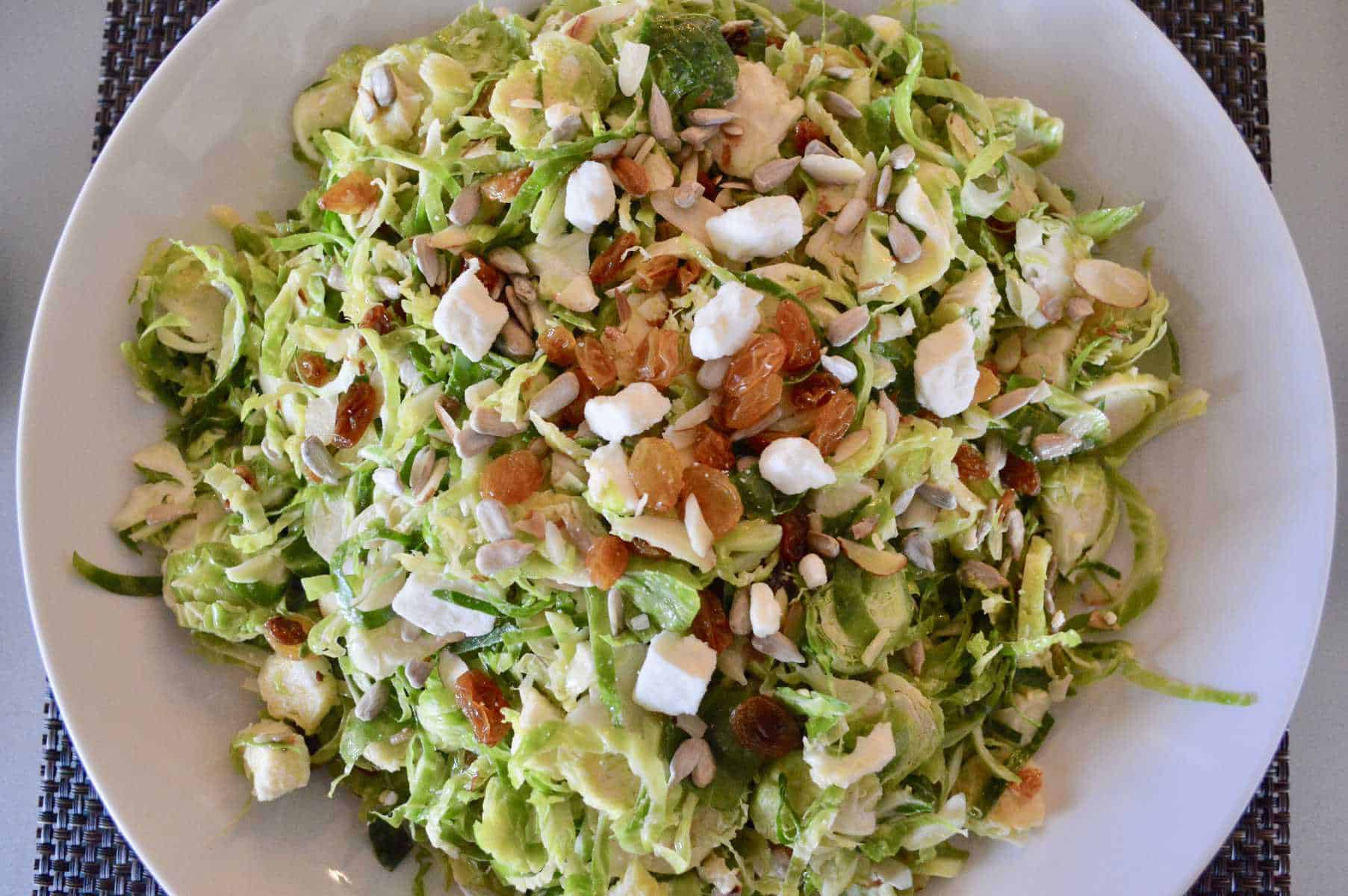 Brussels sprouts Salad with feta raisins and sunflower seeds in a white bowl