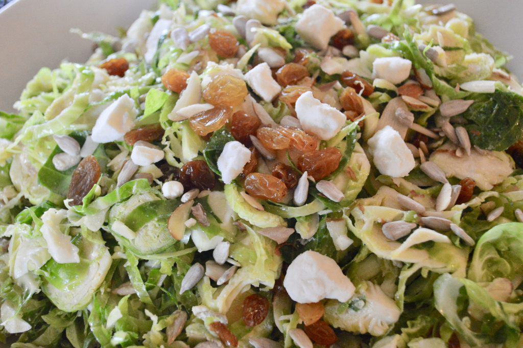 Brussels sprouts Salad with feta raisins and almonds in white bowl
