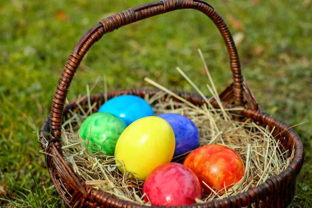 Easter basket full of colorful eggs sitting in a field for Easter Brunch Menu.