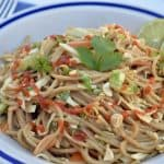 asian noodle salad in a white bowl with lime slices