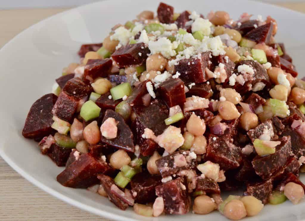 Beet salad with garbanzo beans, feta, celery, and red onion in a white serving bowl.