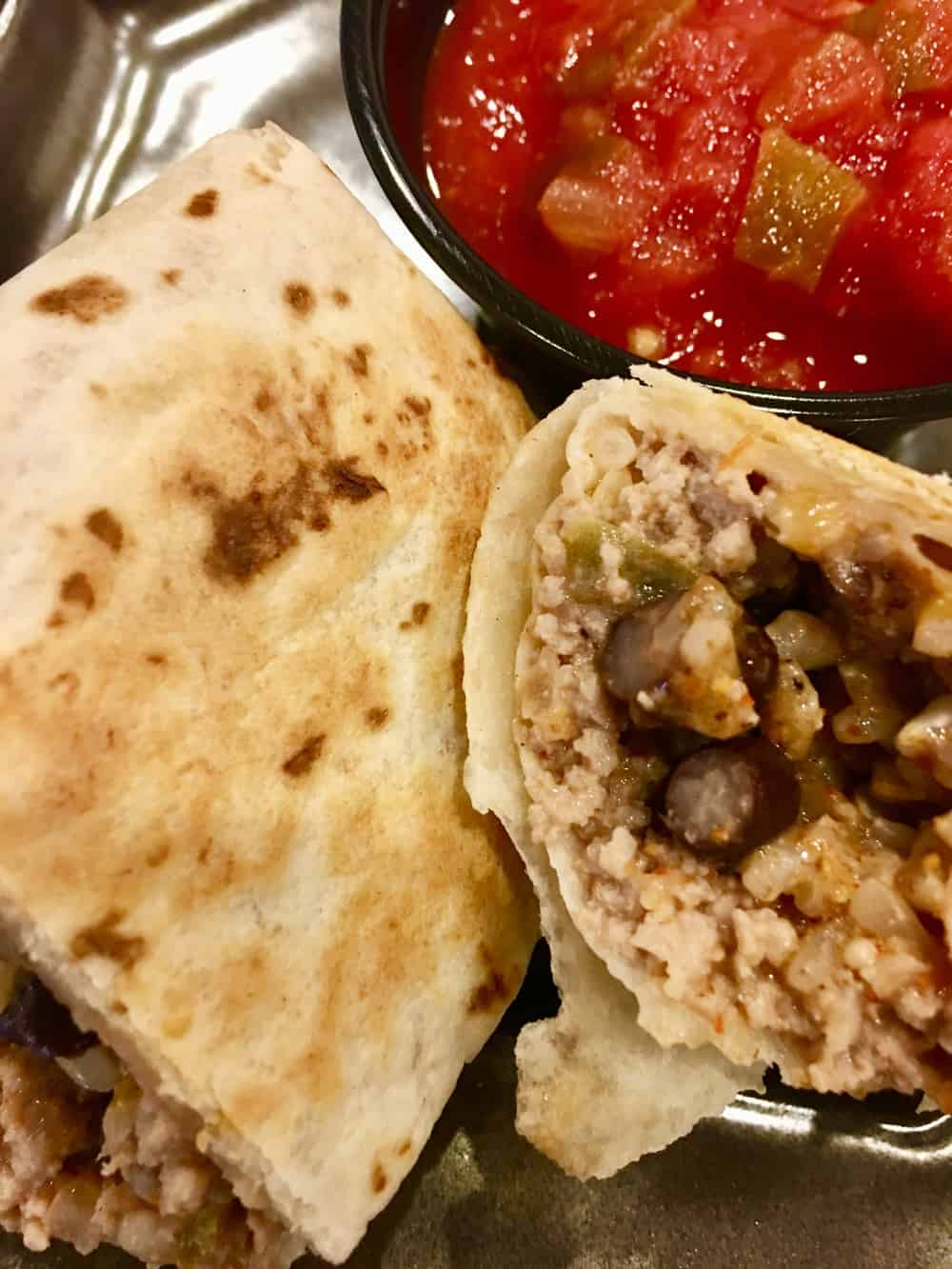 Freezer Burritos with ground turkey, brown rice, black beans, and cheddar cheese is an easy recipe for make ahead burritos that you freeze. Healthy and full of protein, these are a great weeknight dinner or meal prep food. #freezerfoods #freezerburritos #burritos #makeahead #mealprep #groundturkey #healthy #parenting #protein #easyrecipe #weeknightdinner #blackbeans