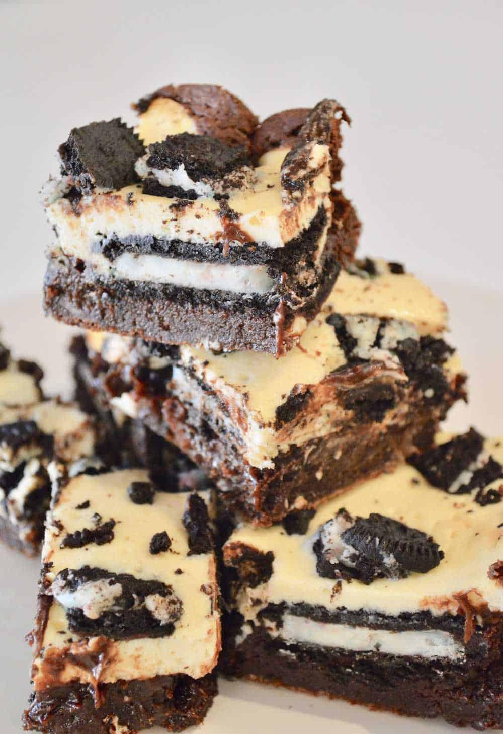 Oreo Cheesecake Brownie Bars piled on a white plate
