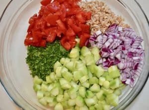 tomatoes, cucumbers, red onion, farro, and parsley in a large glass bowl.