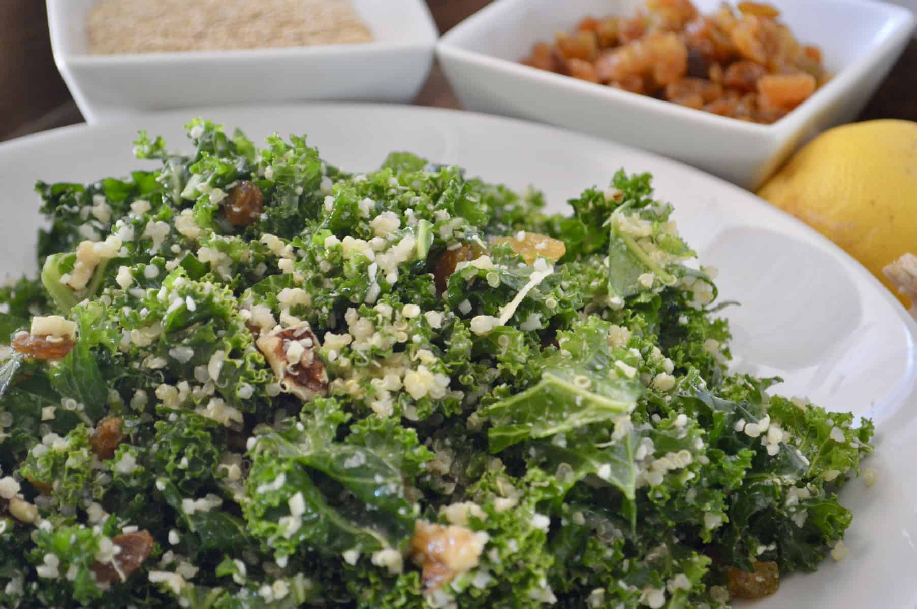 Kale Quinoa Salad with golden raisins and parmesan in a white serving bowl
