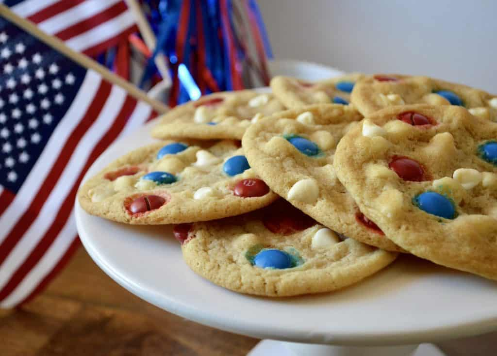 4th of July Cookies with red white and blue m&m's sitting on a white pedestal