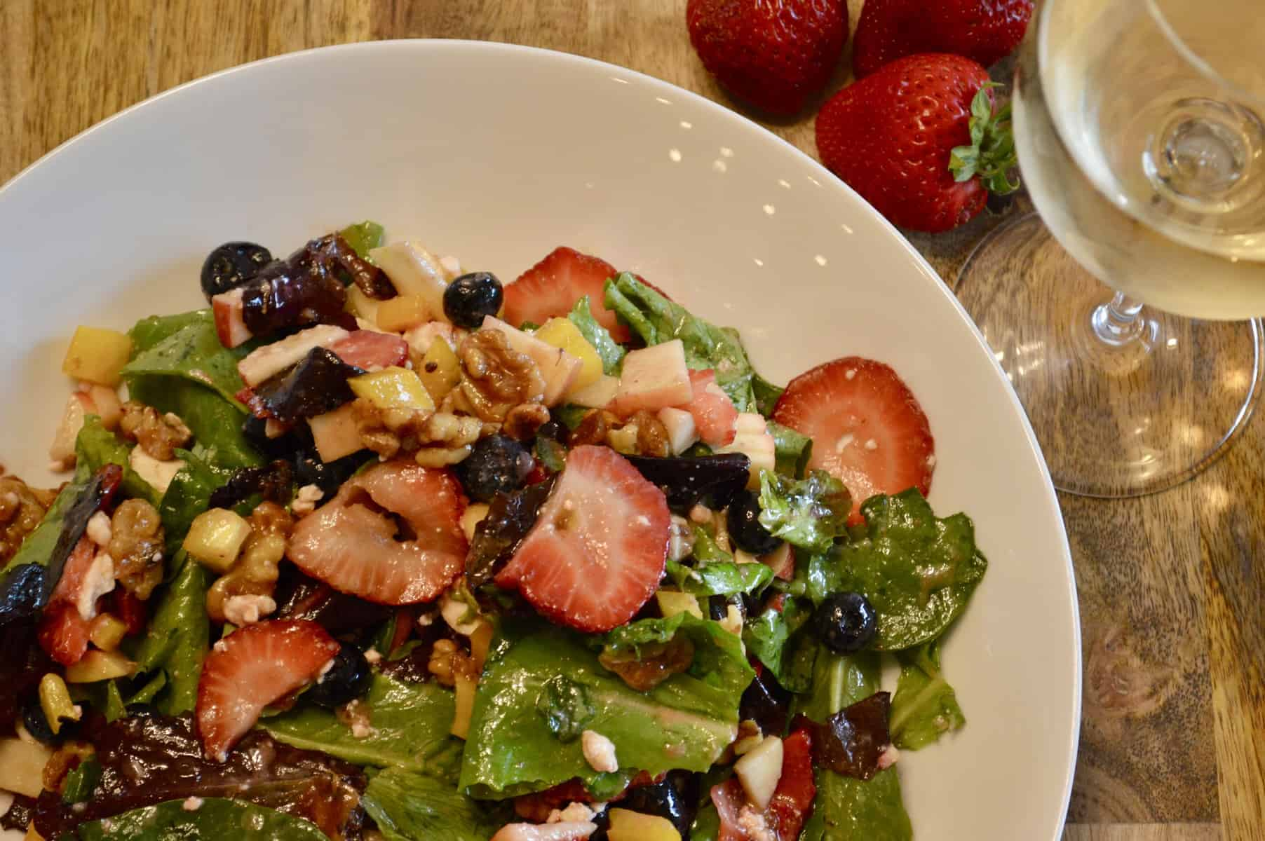 berry salad with candied walnuts on a wood table with a wine glass and strawberries