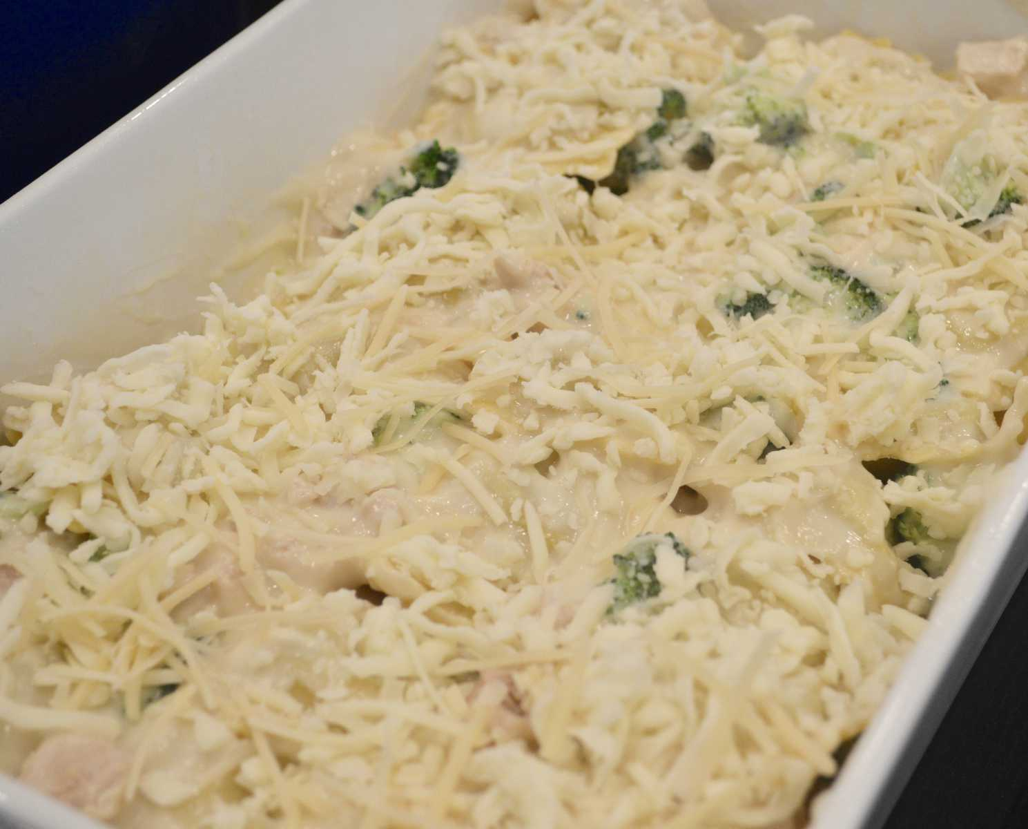 ravioli layered in a baking dish with cheese on top