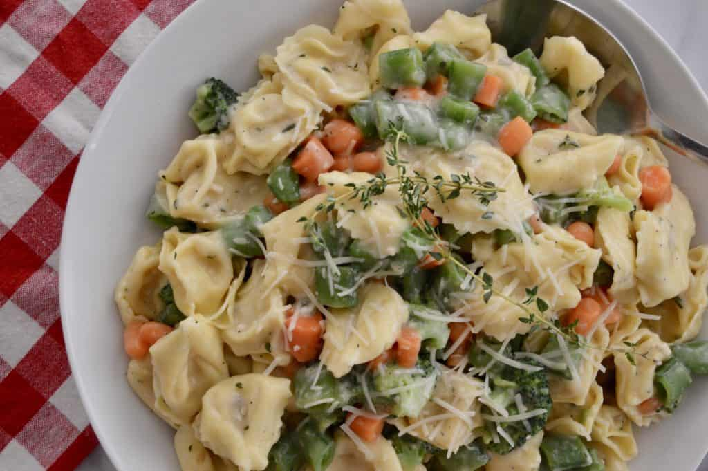 tortellini with veggies and parmesan cheese on top in a white bowl.