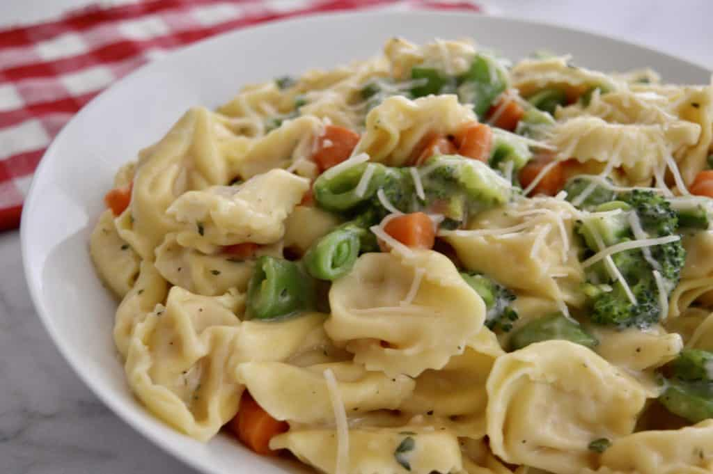 close up of tortellini with carrots, peas, and broccoli in a white plate.