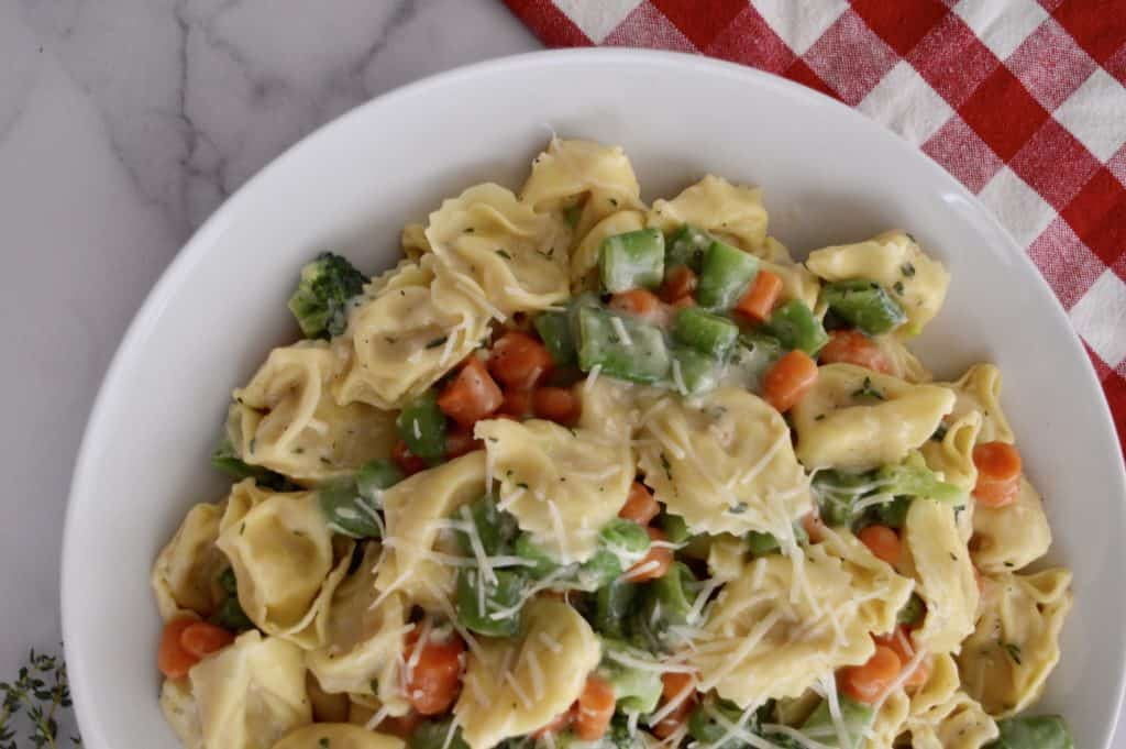 tortellini primavera in a white dish with a checkered napkin in the background.