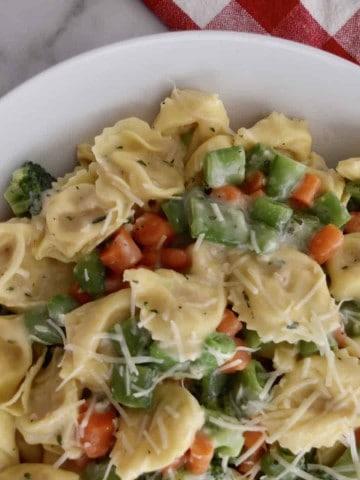 tortellini primavera in a white dish with a checkered napkin in the background.