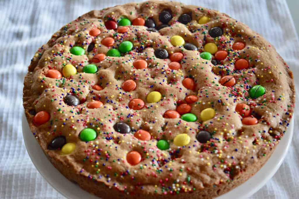 Loaded Cookie Pie can be a great birthday cake or served like cookie pizza. Make with M&M's, Sprinkles, and chocolate chips, this easy recipe is so fun to make! #cookiepie #cookie #cookiepizza #easy #dessert #birthdaycake #sprinkles #loadedcookie #chocolatechip