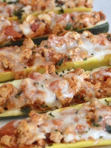 Healthy, low-carb, low-calorie and so easy to make, don't miss these delicious Stuffed Zucchini Boats with Yellow Squash filled with lean ground turkey and tasty Italian flavors.  #weeknightdinner #easyrecipe #healthy #lowcarb #lowcalorie #parenting #zucchini #stuffedzucchini #yellowsquash #groundturkey #healthyitalian