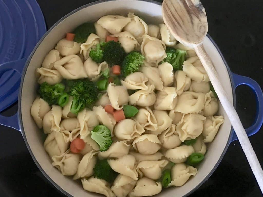 boiling pot of water with pasta and vegetables in it.