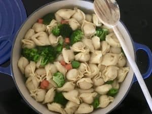 boiling pot of water with tortellini and veggies in it.