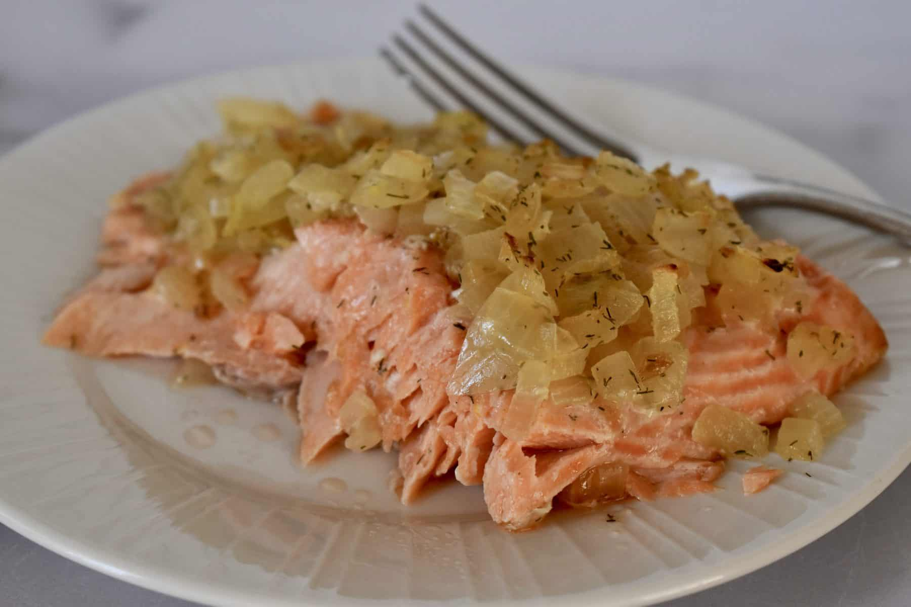 Salmon on a plate with caramelized onions on top.