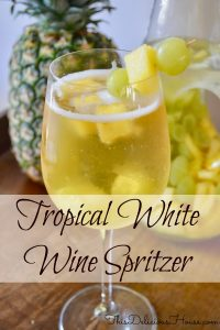 Tropical White wine spritzer in a glass with pineapple and grapes and a pineapple in the background