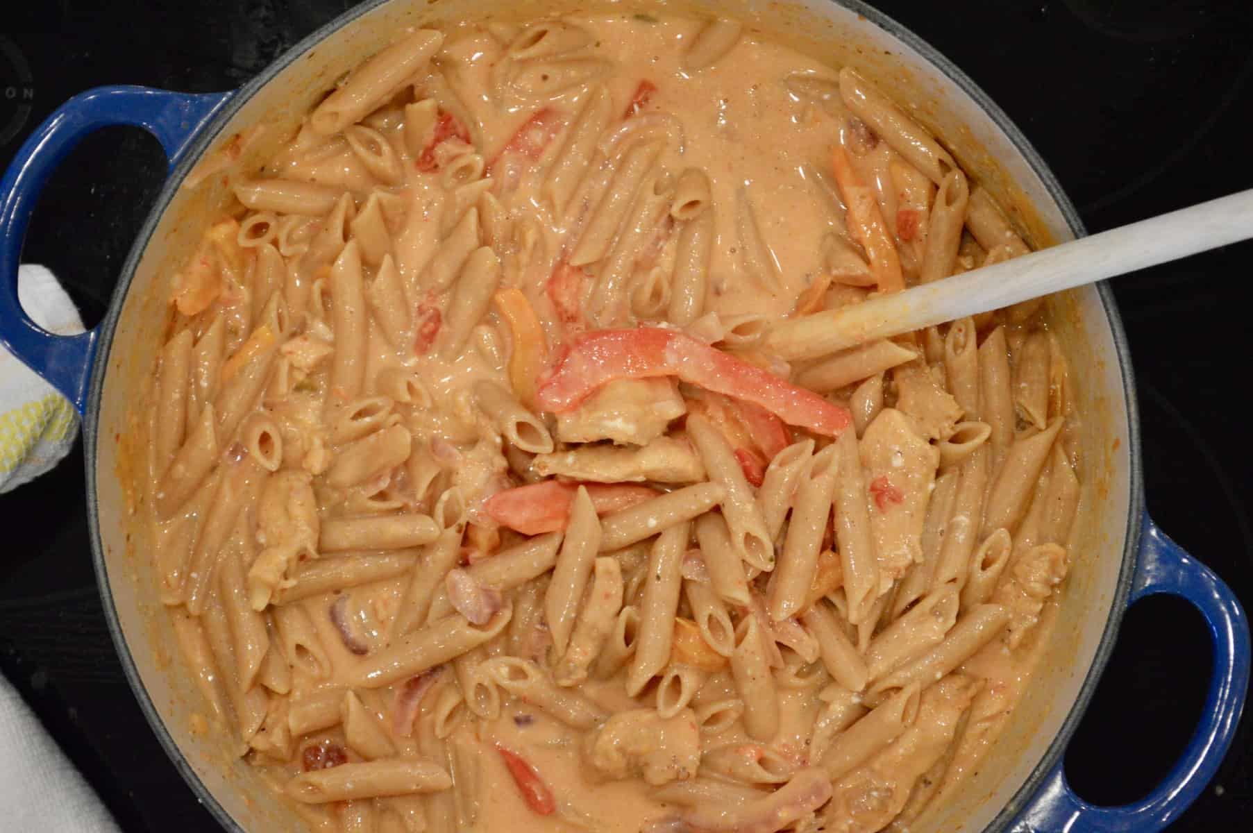 pasta in a large pot with a wooden spoon in it.