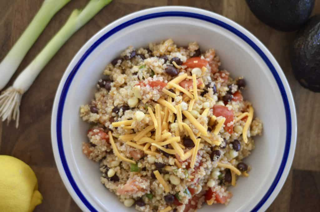 mexican quinoa salad on a wood board with lemon, avocado and green onion