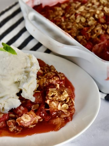 Strawberry Rhubarb Crisp on a white plate with ice cream on top.