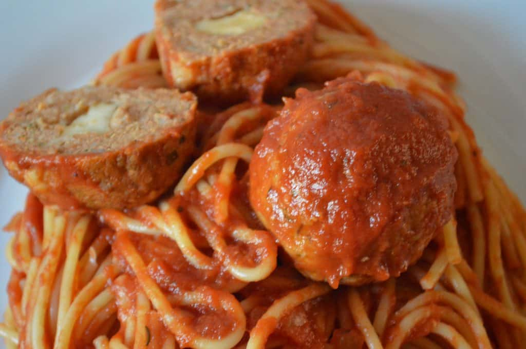 provolone stuffed turkey meatballs with spaghetti on a white plate