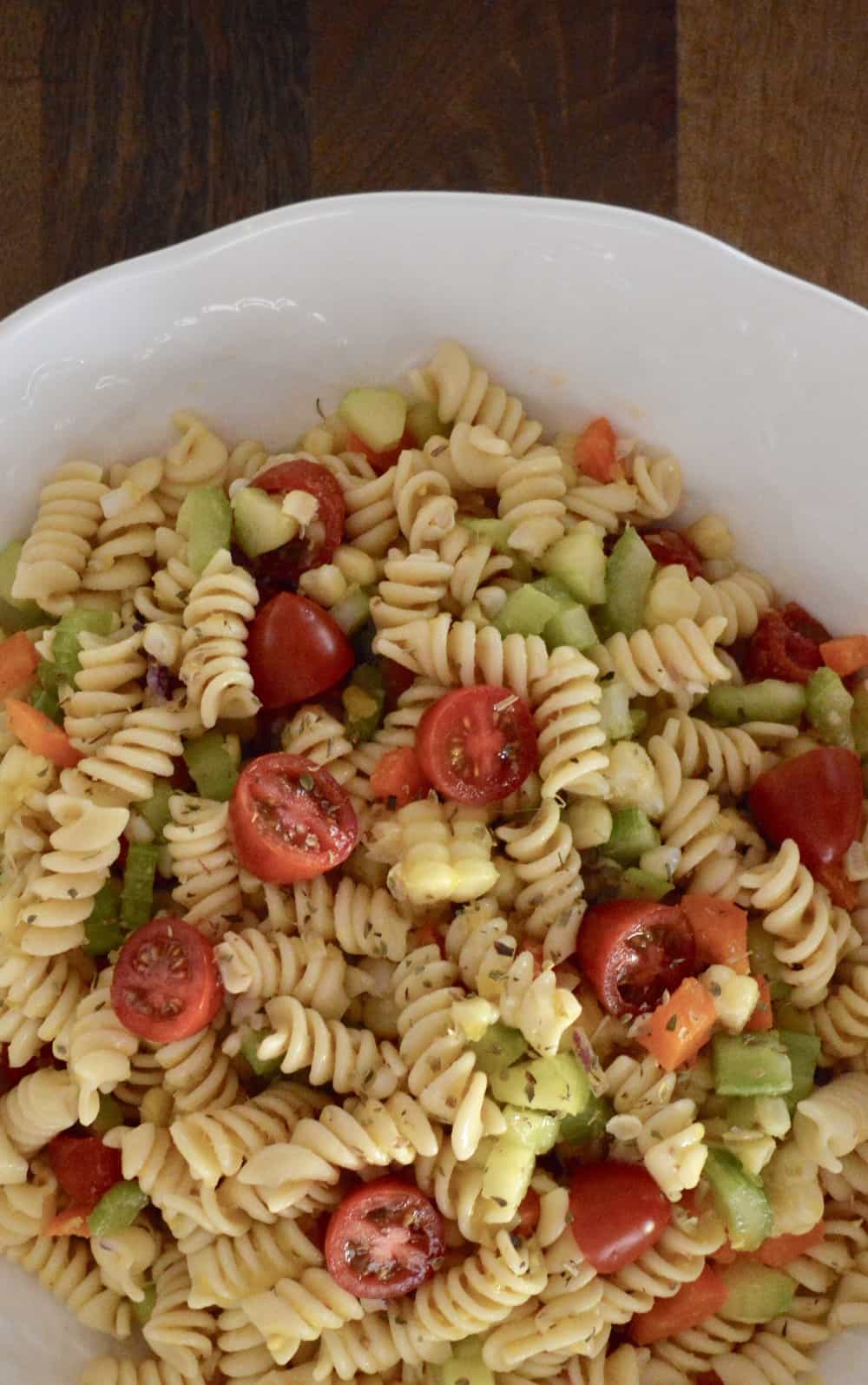 pasta salad with lots of vegetable and corn in a white bowl on a wood surface
