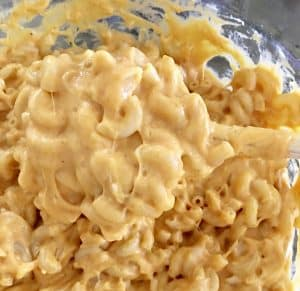 Pumpkin Mac and Cheese in a bowl being tossed together