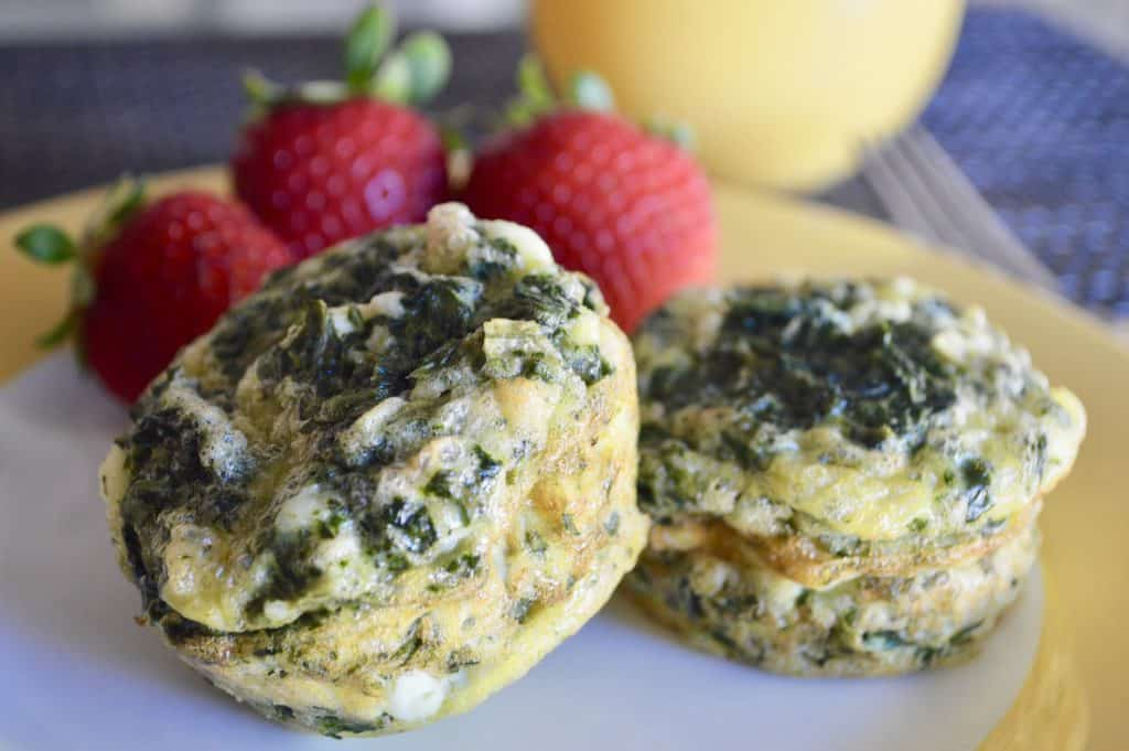 Spinach and Feta Egg Cups on a yellow plate with strawberries
