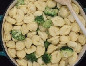 tortellini and broccoli boiling in a pot of water