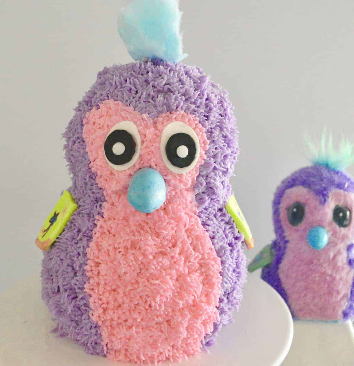 Purple and pink Hatchimals cake on a white pedestal with hatchimal toy in the background.
