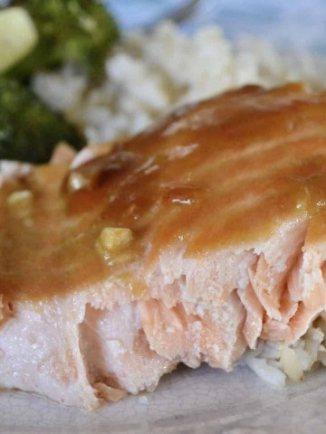 Asian Sesame Salmon on a plate with broccoli and brown rice