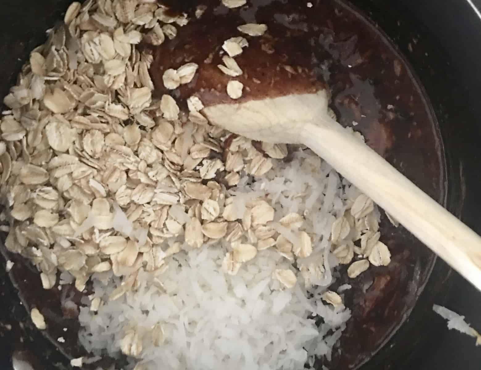 stirring in coconut and rolled oats in the saucepan mixture.