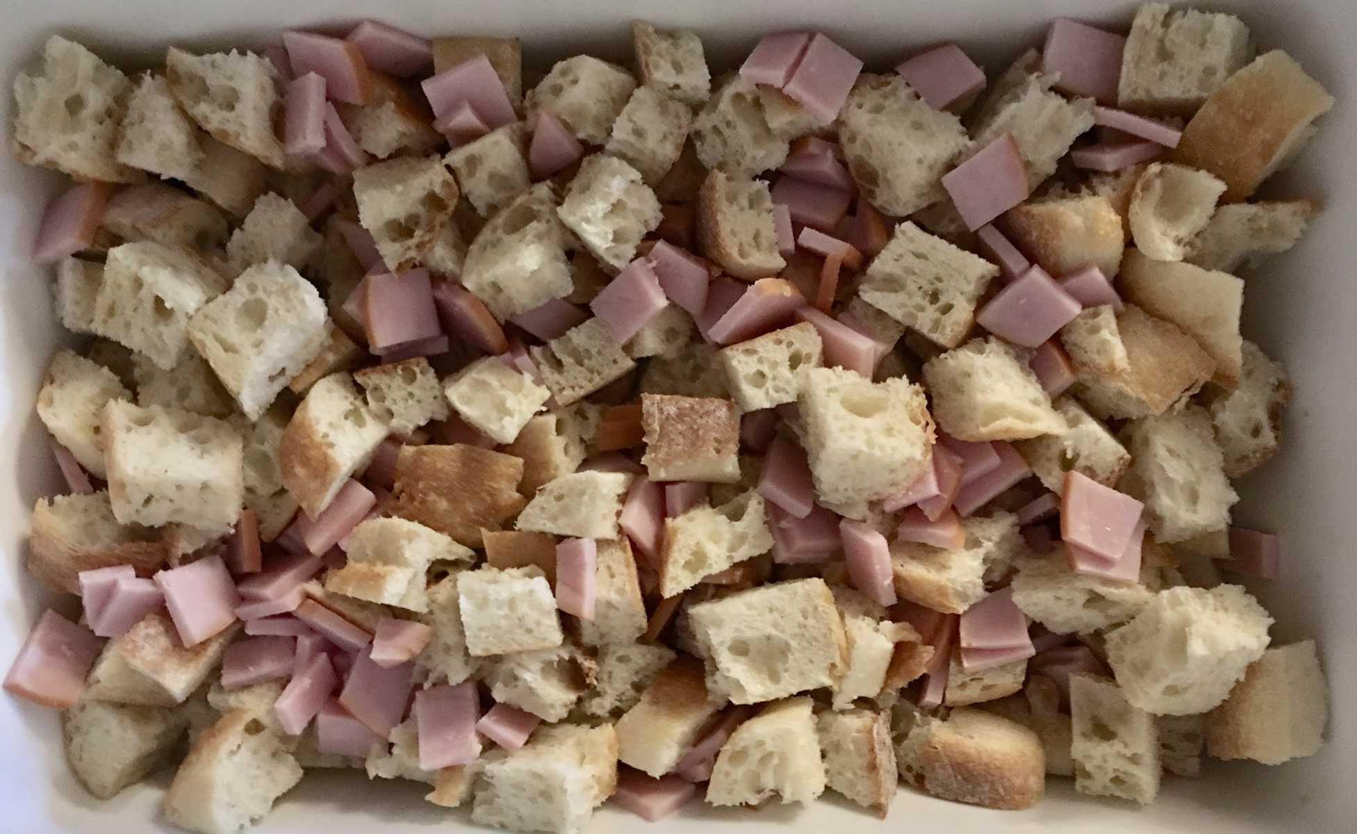 add cut up ham to the bread cubes in the casserole dish.