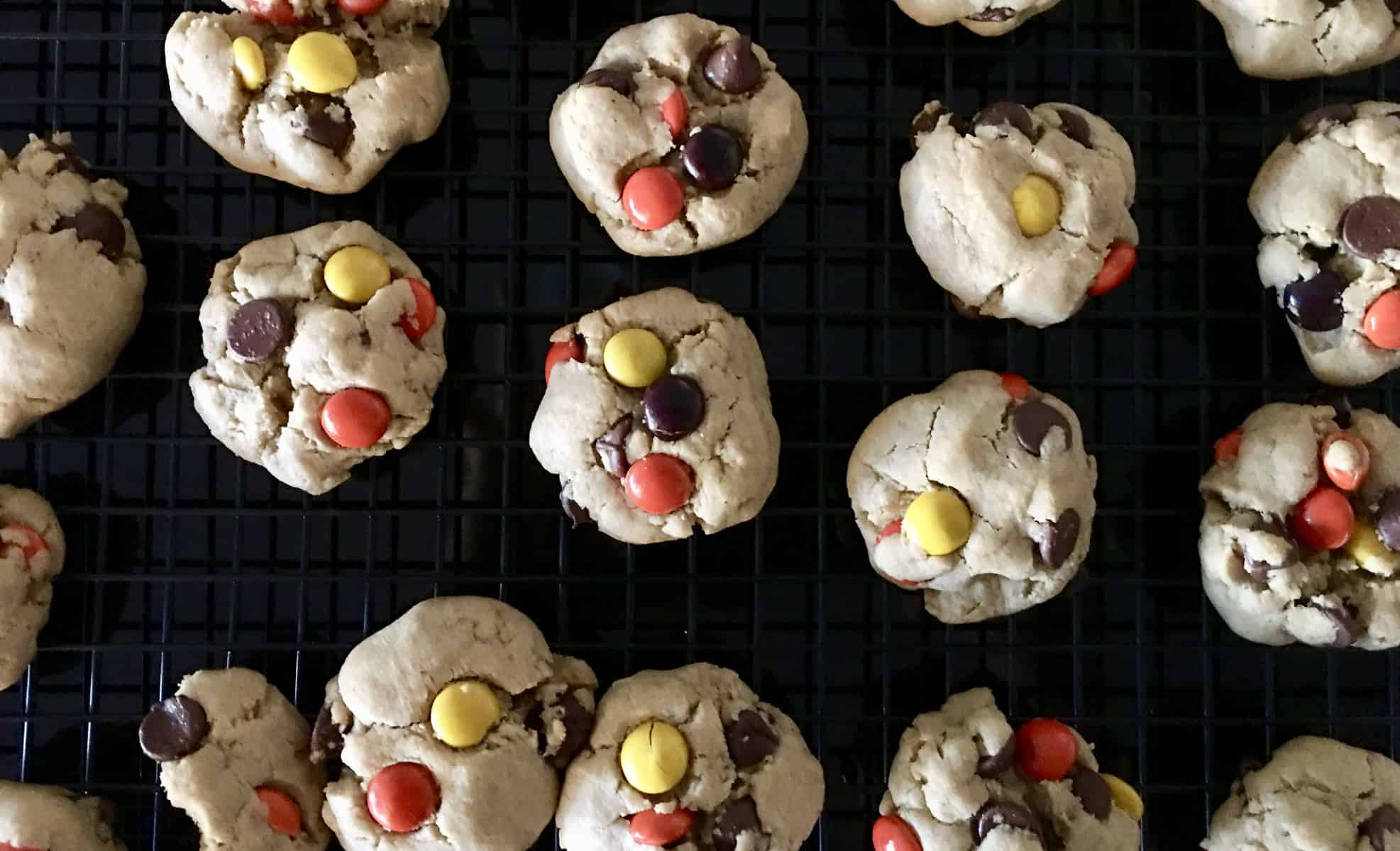Reeses Pieces Peanut Butter Chocolate Chip Cookies on a wire cooling rack.