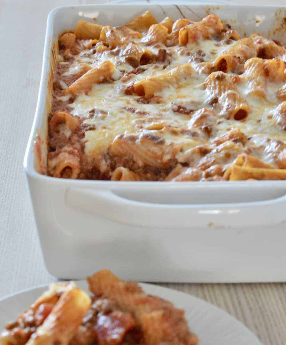 Baked Ziti with meat sauce in a white baking dish.