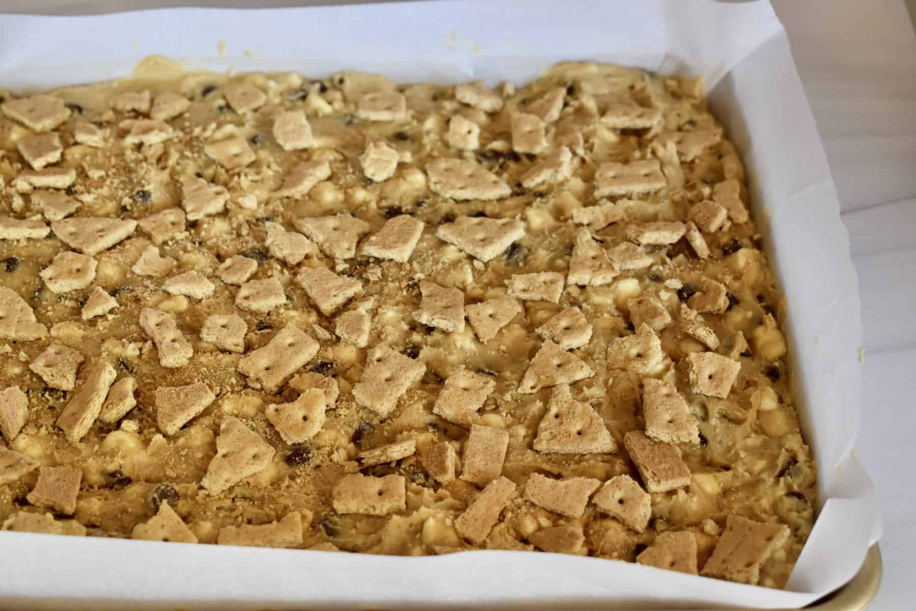 s'mores cookie batter spread on a baking sheet and topped with graham cracker.