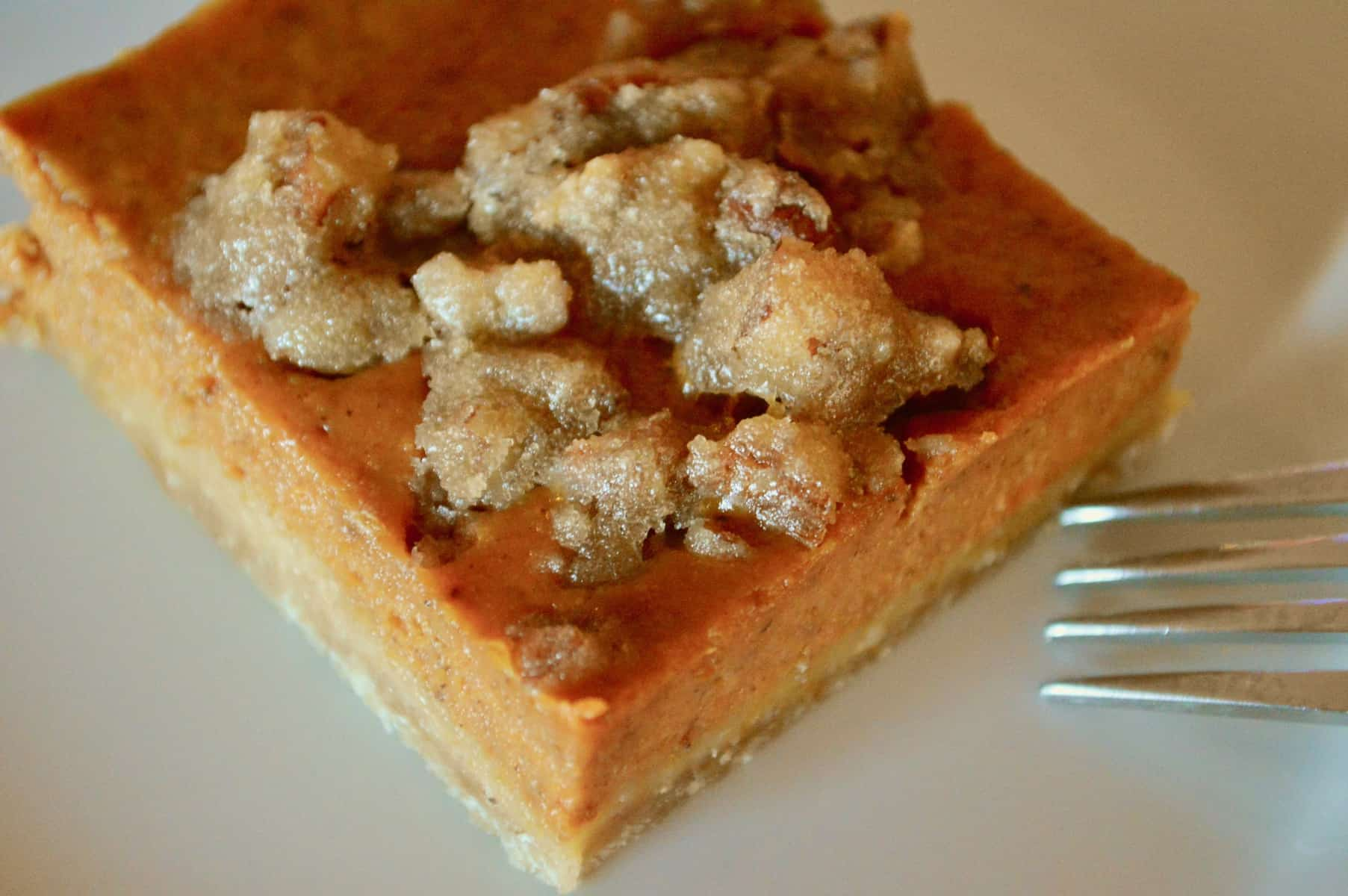 pumpkin pie bars on a white plate with a fork next to it.