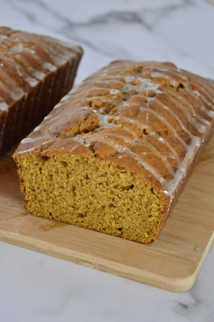 glazed pumpkin bread on a cutting board.