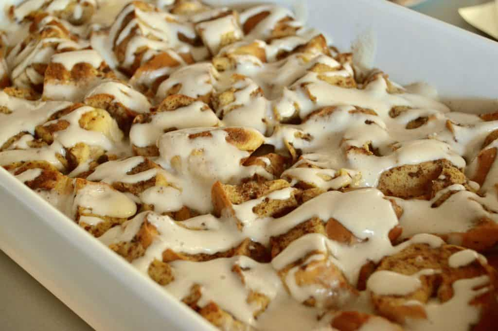 overnight bagel French toast casserole with a cream cheese maple glaze poured overtop.