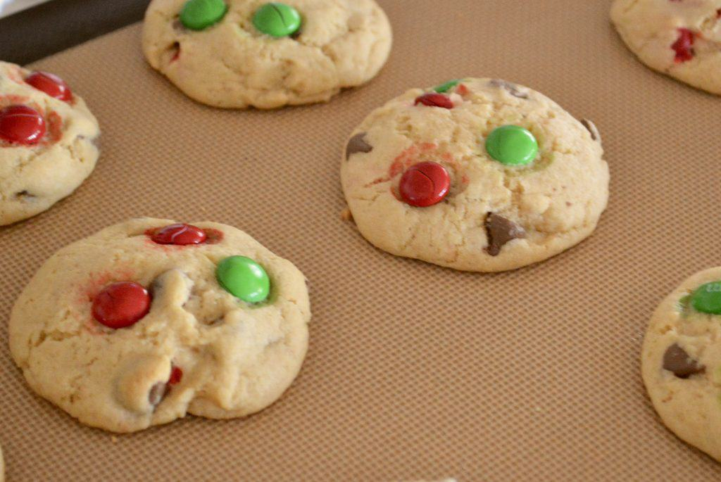 Christmas M&M Cookies out of the oven cooling on a baking mat