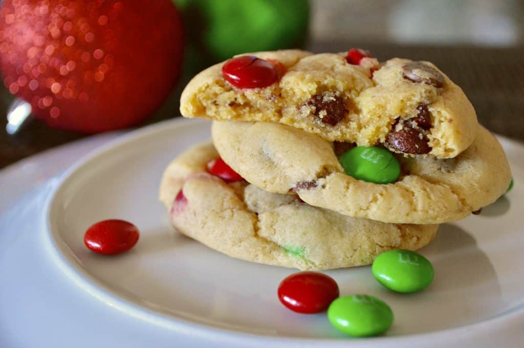 Christmas M&M Cookies on a white plate with red and green ornaments in the background