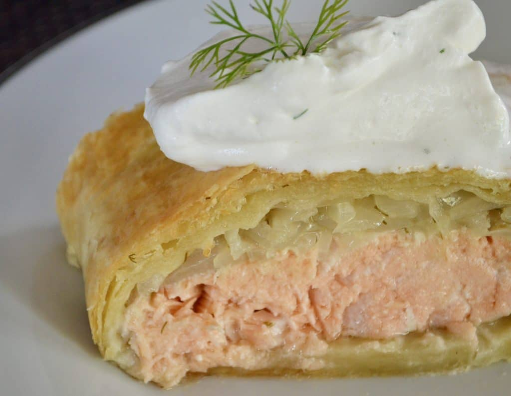 Salmon Wellington topped with caramelized onions, wrapped in puff pastry, and served with dijon dill cream sauce.