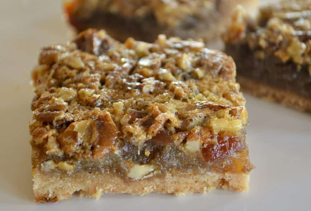 Pecan Pie Date Bars on a white plate with bars in the background