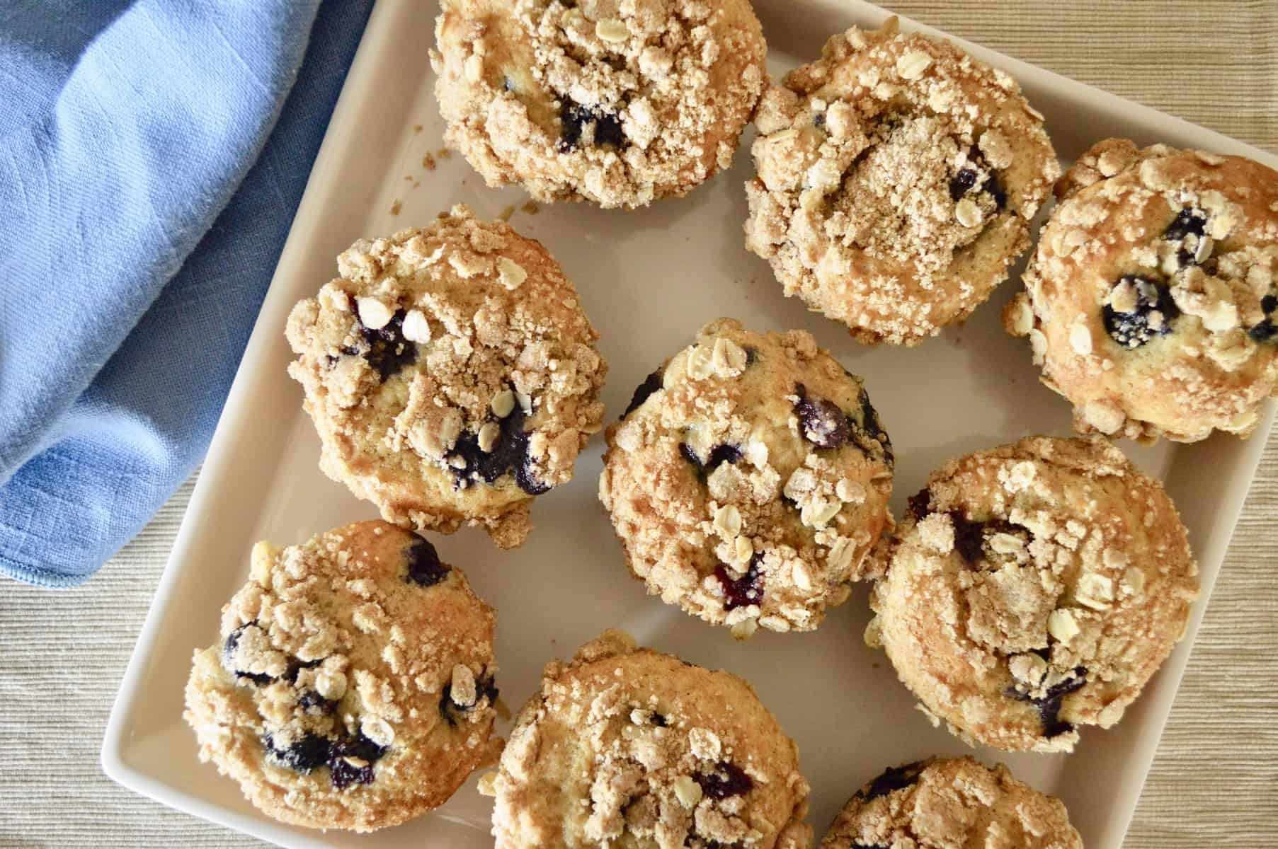 Blueberry Streusel Muffins on a white plate with a blue napkin