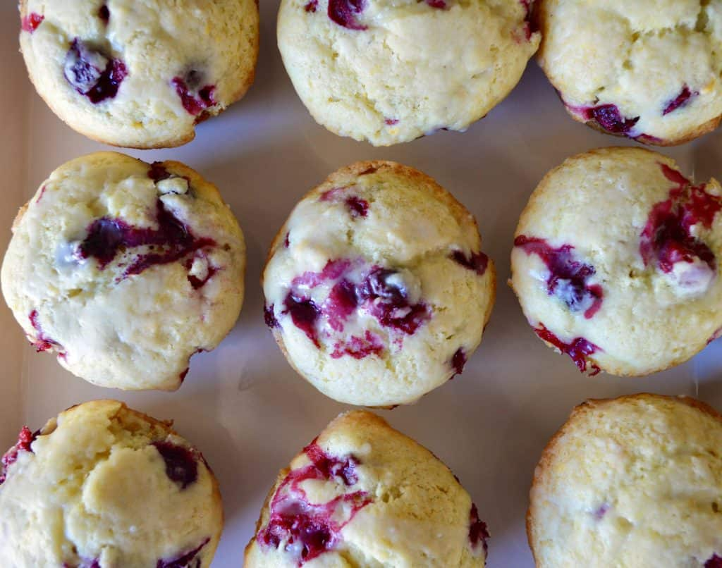 Cranberry orange Muffins with glaze on a white plate