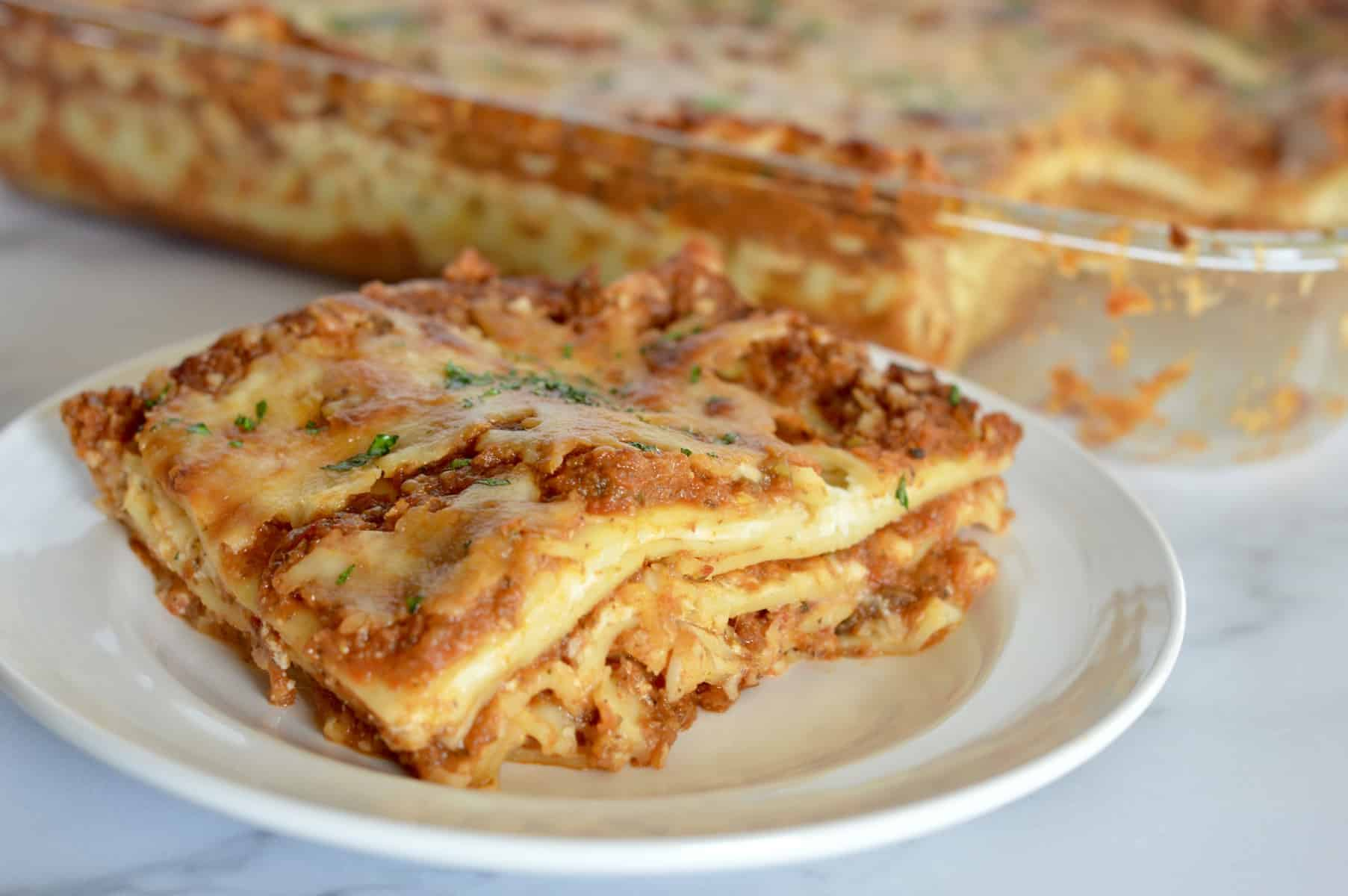 veggie lasagne on a white plate with a pan of it in the background